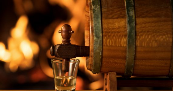 Cachaça being poured into a small glass from a barrel with a fireplace on the background