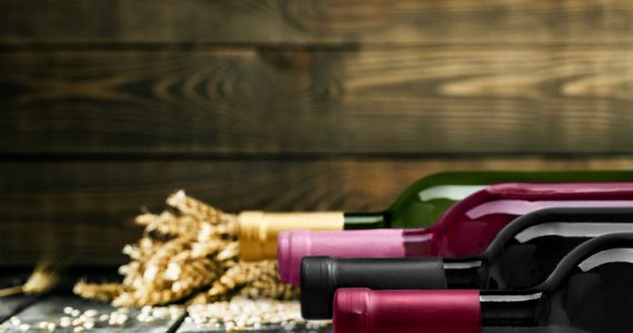 Wine bottles in row on table with wooden background